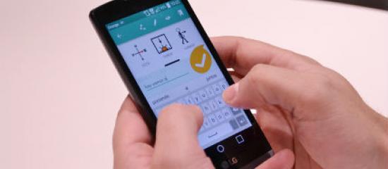 Interfaz de la aplicación en la pantalla de un móvil que sujetan dos manos.