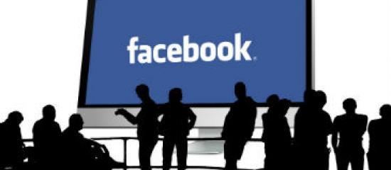 Foto de adorno. Un grupo de personas delante de una gran pantalla que pone Facebook